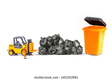 miniature worker and forklift with black garbage bag isolated on white background, image for cleaning and ecology concept.