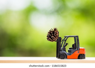 miniature worker with forklift and pine cone on blurred green garden background for Christmas decorative.