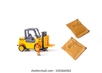 miniature worker and forklift with white and brown sugar bag on white background.