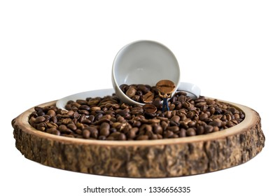 miniature worker holding coffee bean with white cup on wooden plate over blurred plantation of coffee tree with sun lighting.
