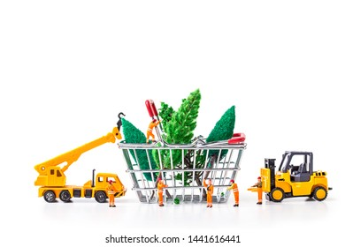 Miniature Worker Passenger Christmas Tree by Truck and forklift to shopping basket isolated on white background ,  Image for Christmas Holiday and Happy New Year Gift Celebration concept.