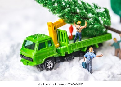 Miniature Worker Passenger Christmas Tree by Truck on snow ,Decoration Image for Christmas Holiday and Happy New Year Gift Celebration concept.