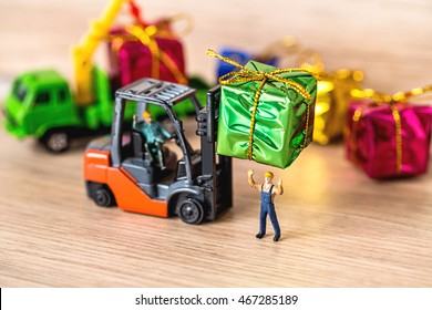 Miniature Worker Passenger Gift Box by Forklift Machine on Wooden floor ,Determined  Image for Christmas Holiday and Happy New Year Gift Celebration concept.