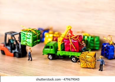 Miniature Worker Passenger Gift Box by Truck on Wooden floor ,Determined Image for Christmas Holiday and Happy New Year Gift Celebration concept.