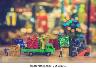 Miniature Worker Passenger Gift Box by Truck on Wooden floor , Image for Christmas Holiday and Happy New Year Gift Celebration concept. vintage tone.