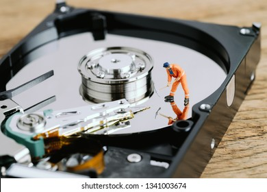 Miniature worker or professional staff digging on HDD, hard drive using as data mining, data restore or fixing and repair computer hardware concept.