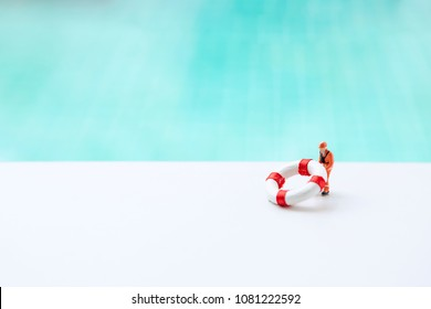 Miniature worker with small life buoy over blurred blue swimming pool water background, life guard, swimming pool and beach safety concept