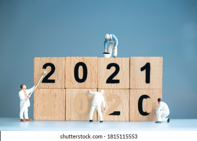 Miniature worker team painted number 2021 and remove number 2020 , Happy new year concept