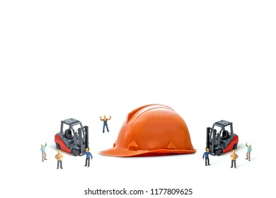 miniature worker with used and old Safety Helmets (Head Protection) on table isolated on white.