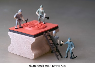 Miniature workers create rubber stamp, manufacturing concept