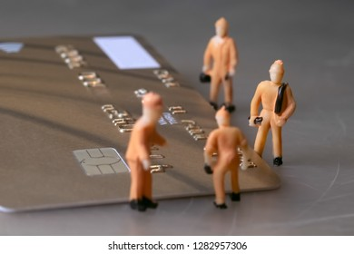 Miniature workers figures repairing golden credit card