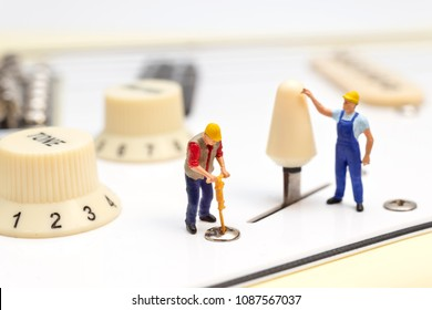 Miniature Workers Fixing The Control Switch Of An Electric Guitar