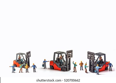 miniature workers standing front of forklift machine, on white background.