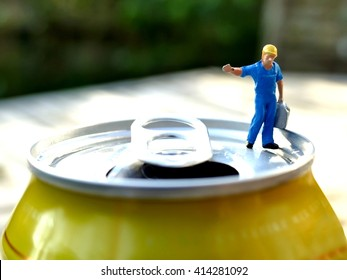 Miniature workman carrying heavy jerrycan on top of soda can with blurred background. Business concept