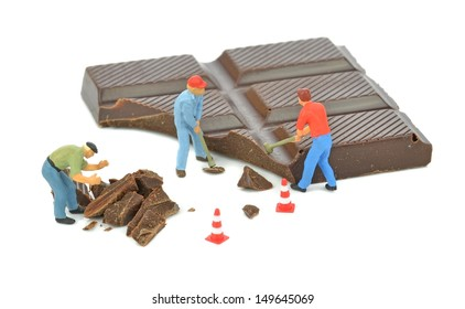 A miniature workman cutting a bar of chocolate with chainsaw