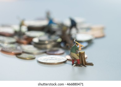 Miniature workmen cutting the tree on pile of coins.