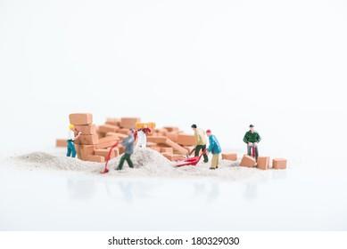 Miniature workmen doing construction work close up