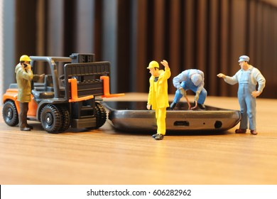 the Miniature workmen inspecting generic cell phone