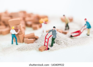 Miniature workmen laying and carrying bricks close up