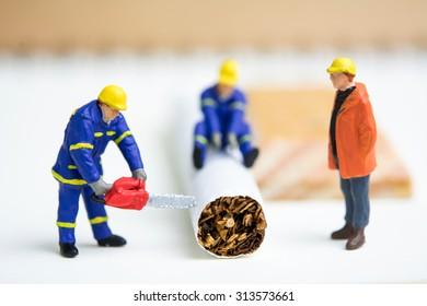 Miniature workmen working together cutting burned cigarette