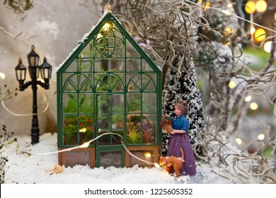 Miniature world: woman with flowers next to a greenhouse