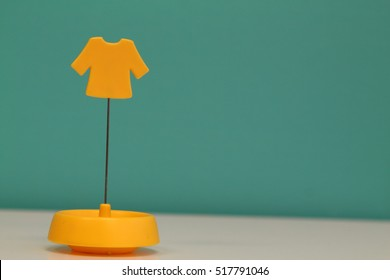 A miniature of a yellow shirt isolated white and blue background