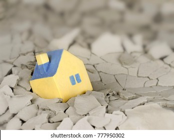 miniature yellow toy house fallen into a crack in the earth.symbol