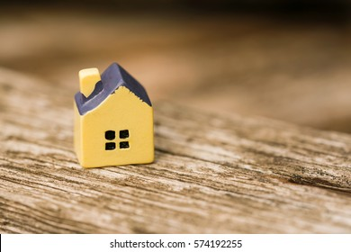 Miniature yellow toy house on a wooden table