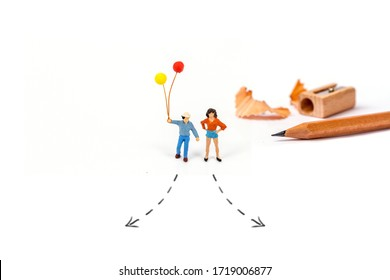 miniature young man, young woman with arrow line and pencil isolated on white background.