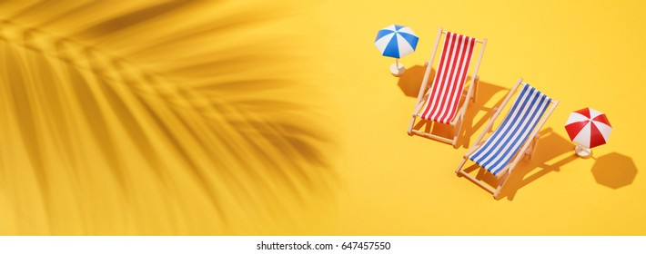 Miniatures beach chair with umbrella and shadow of palm