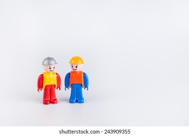 Miniatures of construction workers isolated on white background
