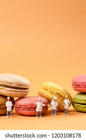 miniatures peoples : chefs in front of delicious macaroons.