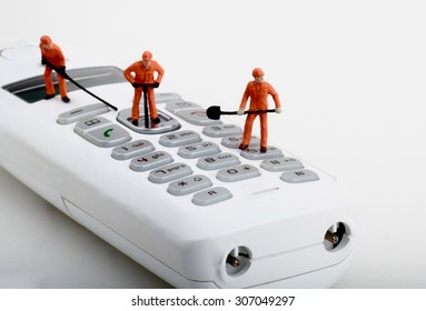 miniatures of workers fixing a cordless phone