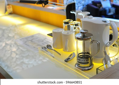 mini-bar corner in luxury hotel room with kettle ,glasses , wine opener and spoons