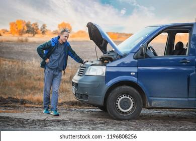 minibus driver near a broken car on the road side. car repair