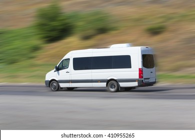 minibus moves on the highway against the hill