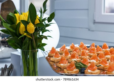 mini-canapes with smoked salmon and razmorinom on a silver platter for a party. Next to the mini canapes is a vase with zolotnye tulips. mini canapes with smoked salmon