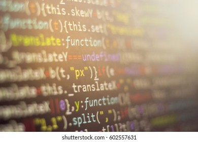 Minificated web development javascript code close up in sunset rays. Abstract information digital technology modern background. HTML5 concept macro backdrop in warm colors. Screen of web developer.