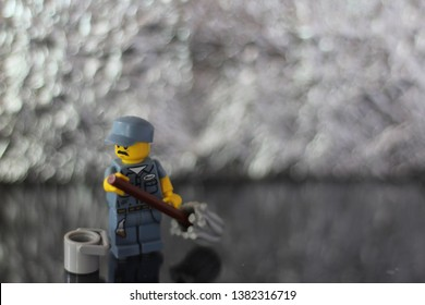 Minifigure of a Lego cleaning man in uniform doing his job. Editorial image, studio shot, macro photography.