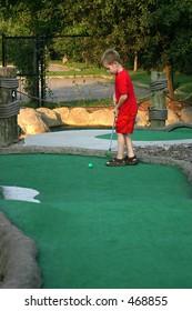 Mini-golf Anyone?  A little boy putts during a game of miniature golf.