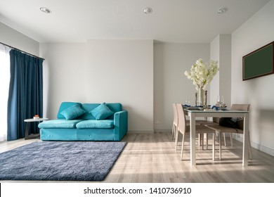 minimal apartment interior design with blue sofa and wooden dining table home interior background