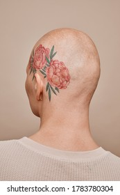 Minimal back view portrait of bald woman with head tattoo posing against beige background in studio, alopecia and cancer awareness