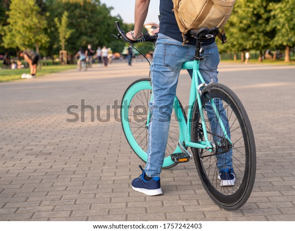minimal bike in the foreground, ridden by a man with a backpack on his shoulders, symbol of freedom and movement in the city, background of green city area