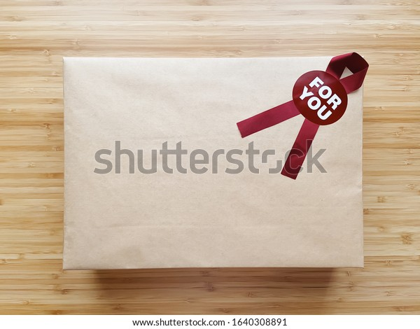 A minimal brown paper gift wrap box with for you ribbon flag lay flat on wooden table on the center of the frame. Close up, top view and isolated on wooden background, with copy space.