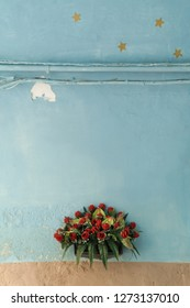 Minimal close up of a bunch of plastic red roses in a pot on an ancient turquoise and brown wall on the streer, with the painting gone and four stars aboves pipes on top, in Bari, Puglia, south Italy.