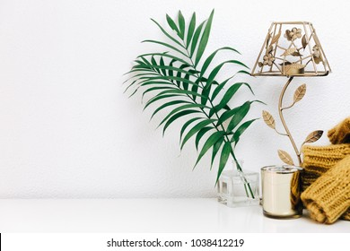 Minimal composition with green tropical leaves, candle and trendy warm sweater. Nordic decorations, Scandinavian style interior