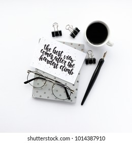 Minimal composition with notepad, calligraphic pen, glasses, mug of coffee, black paper clamps on a white background. Card with quote - the best view comes after the hardest climb