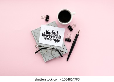 Minimal composition with notepad, calligraphic pen, glasses, mug of coffee, black paper clamps on a pink background. Card with quote - the best things in life are simple