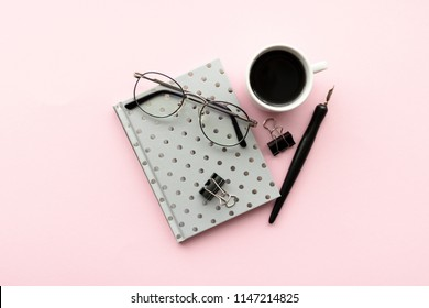 Minimal composition with notepad, calligraphic pen, glasses, mug of coffee, black paper clamps on a pink pastel background