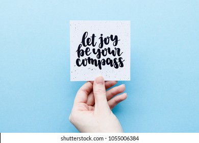 Minimal composition on a blue pastel background with girl's hand holding card with quote -  Let joy be your compass